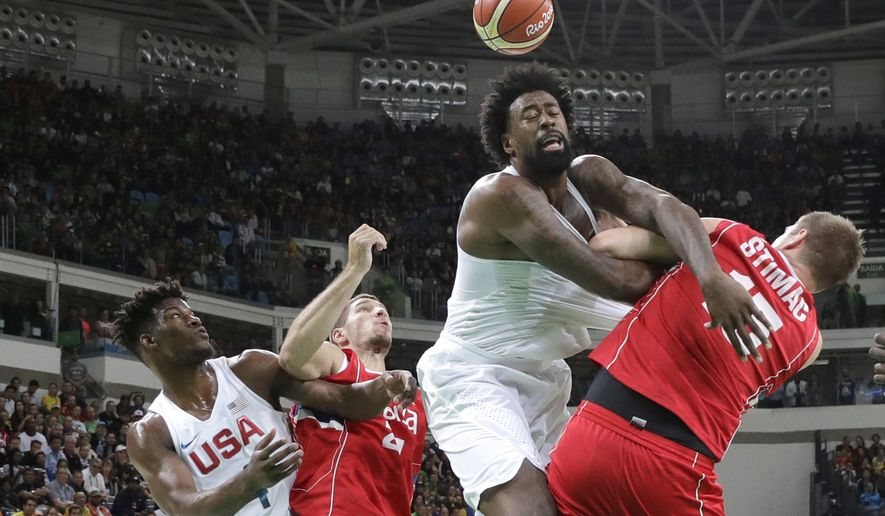 United States' DeAndre Jordan, center, scramble for a rebound with Serbia's Vladimir Stimac, right, during a men's basketball game at the 2016 Summer Olympics in Rio de Janeiro, Brazil, Friday, Aug. 12, 2016. (AP Photo/Eric Gay)