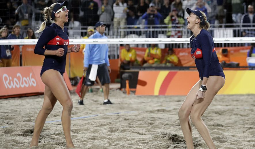United States' Kerri Walsh Jennings, right, celebrates a win over Italy with teammate April Ross during a women's beach volleyball round of 16 match at the 2016 Summer Olympics in Rio de Janeiro, Brazil, Saturday, Aug. 13, 2016. (AP Photo/Marcio Jose Sanchez)
