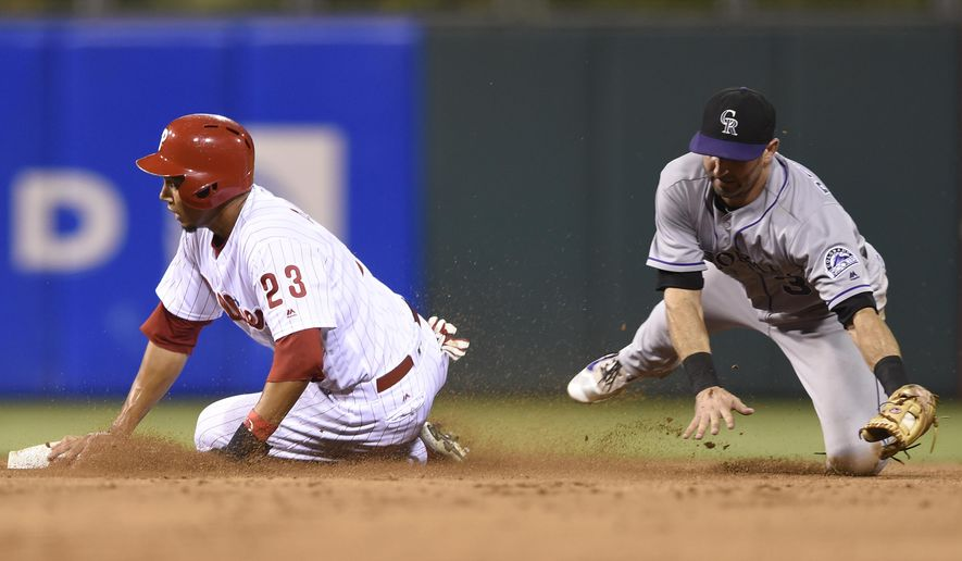 Philadelphia Phillies' Aaron Altherr, left, reaches second base ahead of Colorado Rockies' Daniel Descalso in the second inning of a baseball game on Friday, Aug. 12, 2016, in Philadelphia. (AP Photo/Michael Perez)