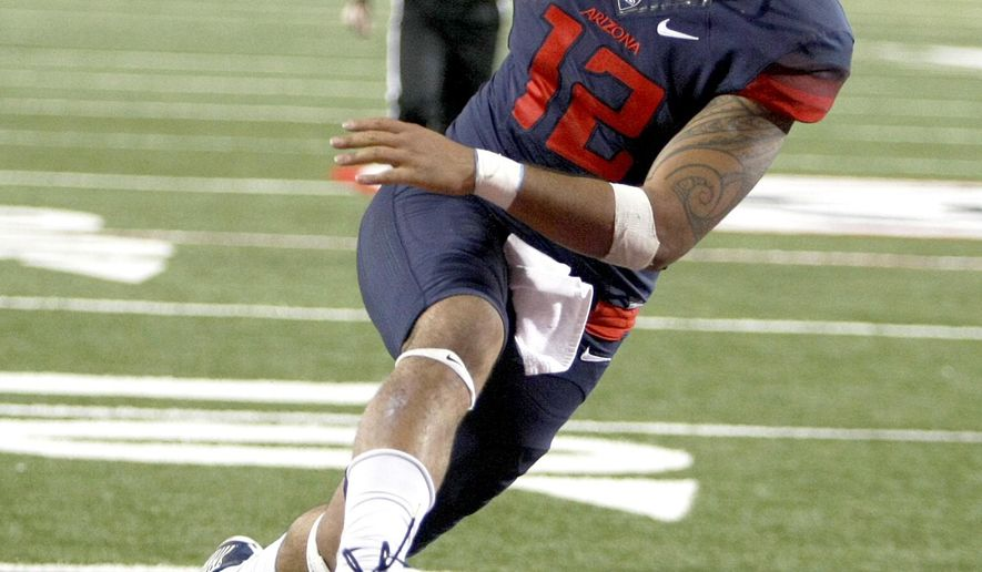 FILE - In this Nov. 14, 2015, file photo, Arizona quarterback Anu Solomon scores a touchdown against Utah during the second half of an NCAA college football game in Tucson, Ariz. (AP Photo/Rick Scuteri, file)