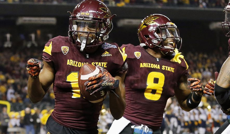 FILE - In this Jan. 2, 2016, file photo, Arizona State receiver Tim White, left, celebrates with teammate Lloyd Carrington after scoring two points after returning a blocked extra-point kick against West Virginia during the first half of the Cactus Bowl NCAA college football game in Phoenix, Ariz. (AP Photo/Ross D. Franklin, file)