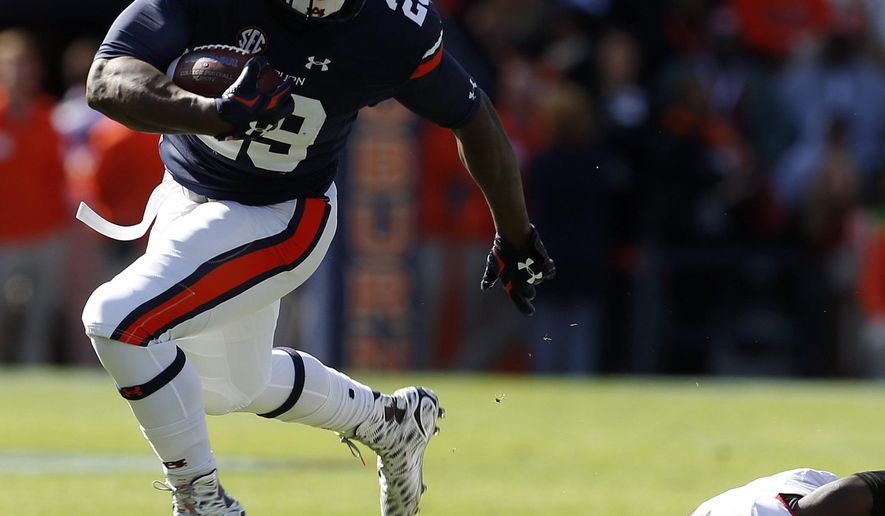 FILE - In this Nov. 14, 2015, file photo, Auburn running back Jovon Robinson (29) carries the ball as he gets around Georgia cornerback Reggie Wilkerson (9) during during the first quarter of an NCAA football game, in Auburn, Ala. Before the Auburn Tigers even started fall camp, amid already diminished expectations, they lost their biggest offensive weapon.Tigers coach Gus Malzahn dismissed Robinson hours before the first practice, leaving a team already seeking a quarterback with another significant void in the backfield. (AP Photo/Butch Dill, File)