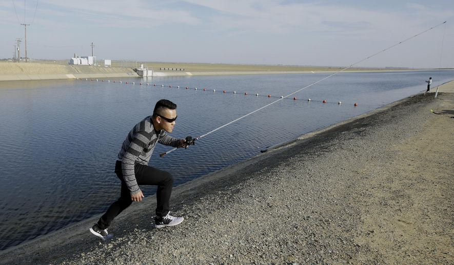 FILE- In this Feb. 25, 2016, file photo, Sha Xinog, climbs the bank to get more bait while fishing along the California Aquaduct near Firebaugh, Calif. Critics and a California lawmaker want more answers from Gov. Jerry Brown's administration on who's paying for a proposed giant water project. That's after a Southern California water district said Thursday, Aug. 11, 2016, that Brown's administration is now stating that state or federal funds will be used to finish planning for two $16 billion water tunnels. (AP Photo/Rich Pedroncelli, File)