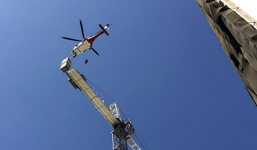 In this frame grab from video, a Los Angeles Fire Department helicopter crew hoists an injured worker off a 270-foot-tall crane in downtown Los Angeles on Thursday, Aug. 11, 2015. Department spokeswoman Margaret Stewart says two paramedics climbed up to the 33-year-old man Thursday afternoon. The worker was unable to climb down but was not seriously hurt. He was safely hoisted aboard the helicopter and taken to Los Angeles County-USC Hospital in fair condition. (AP Photo/Delara Shakib)