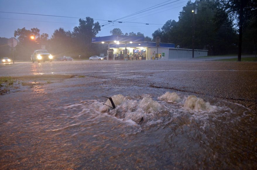 Floodwaters surge from a crack in the parking lot on the corner of highways 584 and 51 in Osyka, Miss., early Friday, Aug. 12, 2016. Flooding is also affecting areas of southwest Mississippi just north of the Louisiana state line.  (Matt Williamson/Enterprise-Journal via AP)
