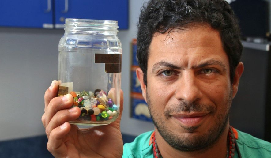 Charles Elmaraghy MD, Chief of the Ear, Nose and Throat Services at Nationwide Children's Hospital holds a collection of what children stuck in their ear, or up their nose on July 6, 2016 in Columbus, Ohio. From just the past couple of months, the jar contains dozens of beads, coins, pebbles and jewels. (Tom Dodge /The Columbus Dispatch via AP)