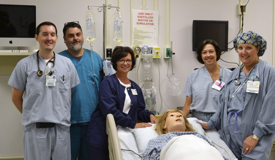 ADVANCE FOR WEEKEND EDITIONS AUG. 13-14 - From left: Dr. David Mullins, Mike Mincek, Leah Patton, Carol McIlhenny and Jodie Babich pose with the Gaumard Scientific obstetrical mannequin Noelle at Conemaugh Memorial Medical Center in Johnstown, Pa. Noelle Birthing Simulator, made by Gaumard Scientific Co., Florida, is a full-size mannequin used to help nurses, residents and physicians practice real-life emergencies. (Vicki Rock/Daily American via AP) MANDATORY CREDIT