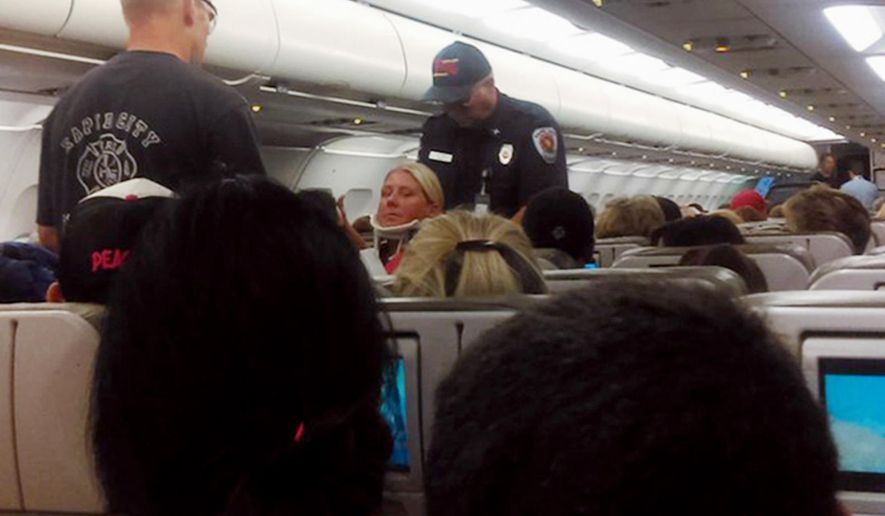 This Thursday, Aug. 11, 2016 photo provided by Rhonda Lynam shows a crew member in a neck brace being removed from a JetBlue aircraft after it landed at the airport in Rapid City, S.D. JetBlue says passengers and crew members were injured when turbulence rocked their flight from Boston to Sacramento, forcing the aircraft to be diverted to South Dakota. (Rhonda Lynam via AP)
