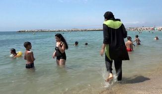 In this Aug. 4 2016, file photo made from video, Nissrine Samali, 20, gets into the sea wearing traditional Islamic dress, in Marseille, southern France. The French resort of Cannes has banned full-body, head-covering swimsuits worn by some Muslim women from its beaches, citing security concerns. A City Hall official said the ordinance, in effect for August, could apply to burkini-style swimsuits. (AP Photo, File)