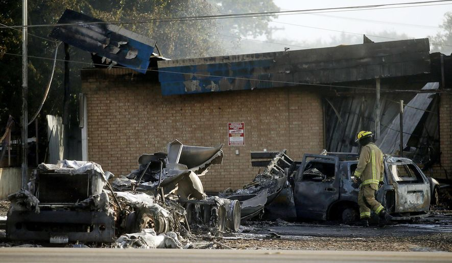 A firefighter works the scene of a fire after a tanker truck exploded at Mickey's Convenience Store, in Killeen, Texas,  Friday, Aug. 12, 2016. Police say preliminary information indicates the tanker truck was refueling the gas pumps when it was struck by an SUV. (Eric J. Shelton /The Killeen Daily Herald via AP)