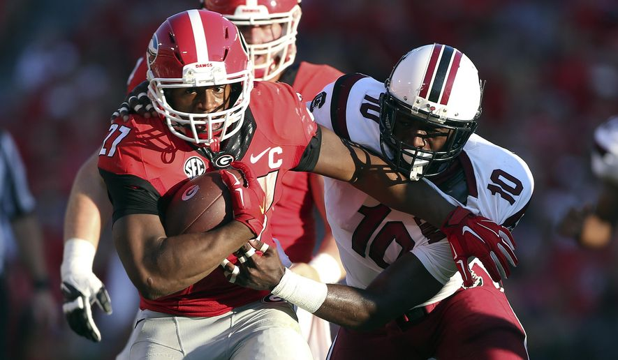 FILE - In this Sept. 19, 2015, file photo, Georgia running back Nick Chubb (27) tries to break free from South Carolina linebacker Skai Moore (10) during the first half of an NCAA college football game in Athens, Ga. Chubb had 747 yards rushing with seven TDs when he tore all the ligaments except the ACL in his left knee on the first play of the sixth game against Tennessee last season. Offensive coordinator Jim Chaney said Chubb looks strong in his comeback. (AP Photo/John Bazemore, File)