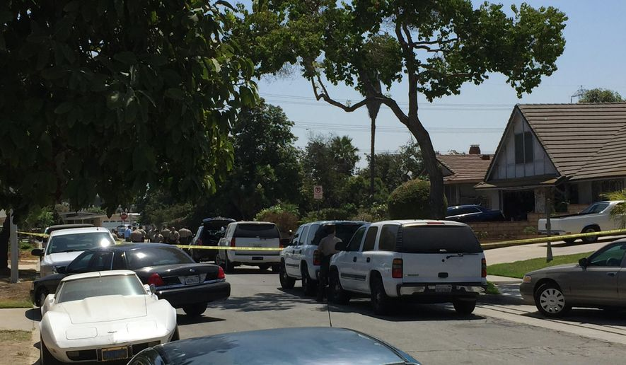 Los Angeles County Sheriff's Department Homicide detectives investigate the fatal stabbing of Elena Moore, a 16-year-old girl inside her two-story home, pictured on the right, Friday, Aug. 12, 2016 in Los Angeles. The Sheriff's department is seeking her 17-year-old ex-boyfriend Rory Murga, in the killing. (AP Photo/Amanda Lee Myers)
