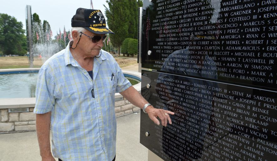 ADVANCE FOR WEEKEND EDITION AUG. 13-14 - In this Aug. 7, 2016 photo Ronald Veverka places his fingers over the name of his late son, David Veverka, which is etched on the War on Terror Memorial located in America's Cemetery in Hermitage. Pa. David Veverka, a sergeant in the U.S. Army, was killed in action 10 years ago in the Iraq War. The memorial currently lists the names of 7,307 U.S. military who were killed while fighting terrorism. (Michael Roknick/The Herald via AP) MANDATORY CREDIT