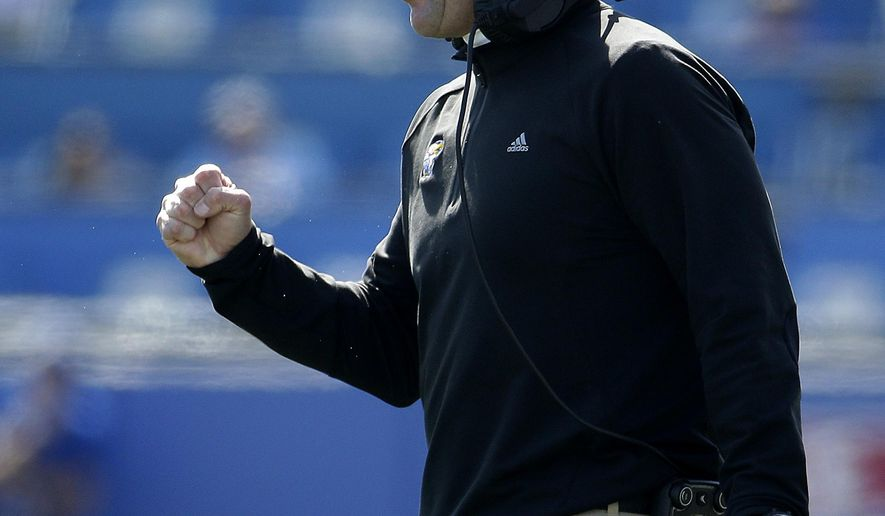 FILE - In this Oct. 10, 2015, file photo, Kansas head coach David Beaty encourages his players during the first half of an NCAA college football game against Baylor, in Lawrence, Kan. Beaty claims he understood the magnitude of the rebuilding job he faced when he left his comfortable job as an assistant at Texas A&M to take over long-downtrodden Jayhawks. Then, he became the first head coach to go 0-12 in school history. (AP Photo/Charlie Riedel, File)