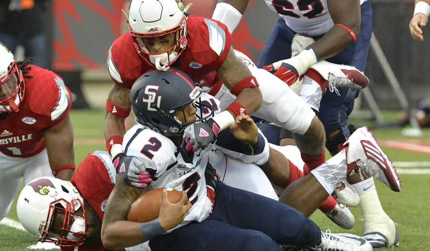 FILE - In this Sept. 26, 2015, file photo, Samford quarterback Michael Eubank (2) is sacked by Louisville nose tackle Deangelo Brown, bottom, and cornerback Jaire Alexander during the first half of their NCAA college football game, in Louisville, Ky. (AP Photo/Timothy D. Easley, File)
