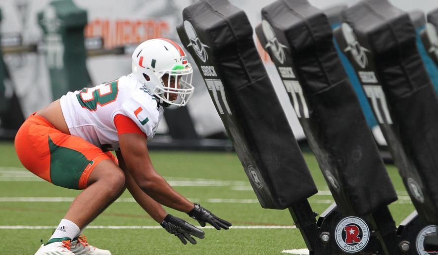 Miami's Trent Harris, left, performs defensive line drills during NCAA college football practice, Thursday, Aug. 11, 2016 in Coral Gables, Fla. (Carl Juste/Miami Herald via AP)