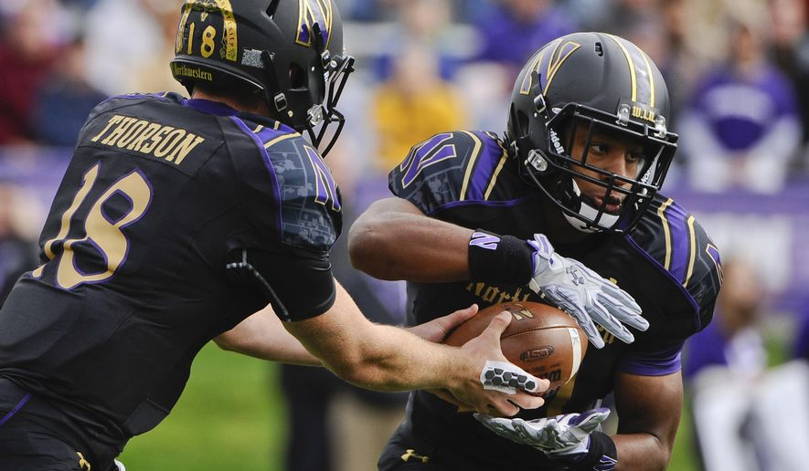 FILE - In this Oct. 3, 2015, file photo, Northwestern quarterback Clayton Thorson (18) hands off to running back Justin Jackson (21) during an NCAA college football game against Minnesota in Evanston, Ill. Thorson did not have to carry a heavy load last year. But now that he has a season behind him, things could change. His development could go a long way toward determining how successful the Wildcats are this season.  (AP Photo/Matt Marton, File)