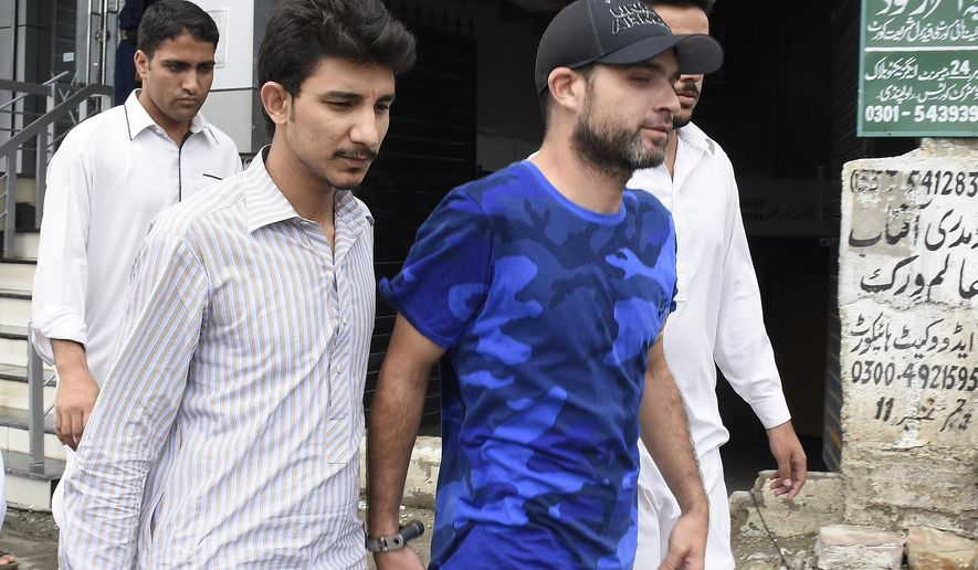 In this photo taken on Tuesday, Aug. 9, 2016, American citizen Mathew Craig Barrett, in blue shirt, is escorted by Pakistani security officials for a court appearance in Rawalpindi, Pakistan. Pakistan's Interior Minister Chaudhry Nisar Ali Khan says, a blacklisted American citizen Barrett will be deported once a joint interrogation team. Barrett, a 33-year-old Alabama native had lived in Pakistan for four years, married a Pakistani woman and had two children. He was expelled from the country in 2011 after being found near a sensitive military installation. (AP Photo/Anjum Naveed)