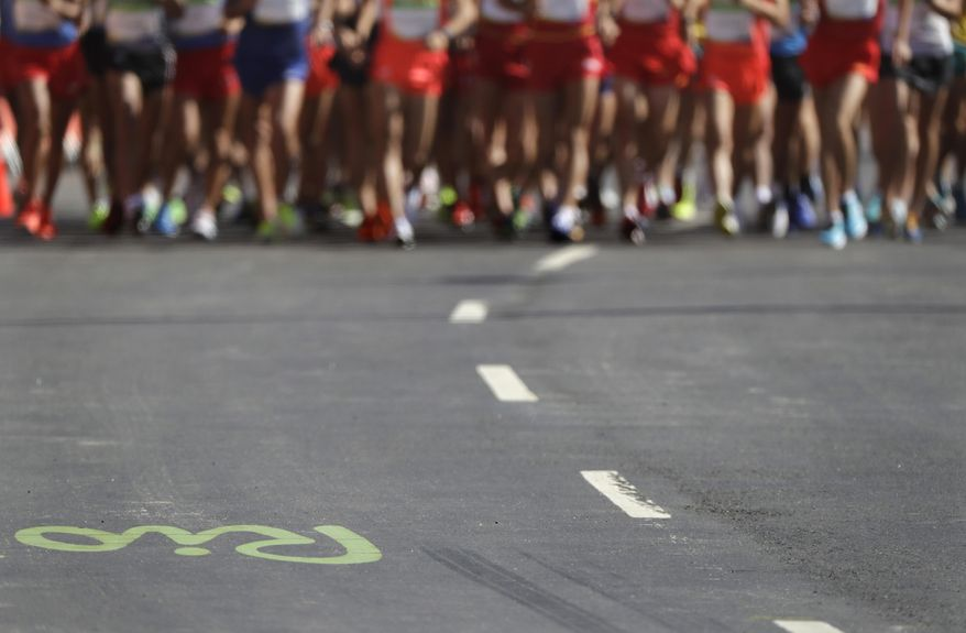 The Rio 2016 logo is painted on the street as athletes make their way at the start of the men's 20km race walk final at the 2016 Summer Olympics in Rio de Janeiro, Brazil, Friday, Aug. 12, 2016. (AP Photo/Jae C. Hong)