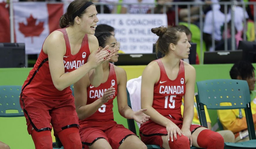 Twin Canada forwards Katherine Plouffe, left, and Michelle Plouffe, right, watch from the bench with guard Kia Nurse during the second half of a women's basketball game against Senegal at the Youth Center at the 2016 Summer Olympics in Rio de Janeiro, Brazil, Wednesday, Aug. 10, 2016. The Plouffe twins have helped Canada advance to the quarterfinals looking for the country's first medal in its sixth Olympics. Canada (3-0) will play the United States (3-0) in group play Friday in a good test of those Canadian medal hopes. (AP Photo/Carlos Osorio)
