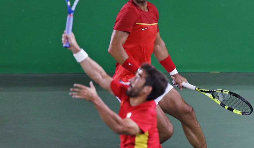 Rafael Nadal, of Spain, top, watches as partner Marc Lopez returns during their match against Romania in the men's doubles final round at the 2016 Summer Olympics in Rio de Janeiro, Brazil, Friday, Aug. 12, 2016. (AP Photo/Charles Krupa)