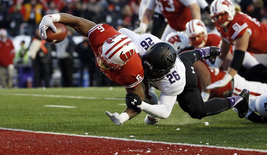 FILE - In this Nov. 21, 2015, file photo, Wisconsin's Corey Clement (6) dives into the end zone in front of Northwestern's Terrance Brown (26) during the second half of an NCAA college football game, in Madison, Wisc. Wisconsin could have a better team, but a worst record, than in 2015.The schedule is that brutal for the Badgers. (AP Photo/Morry Gash, File)