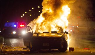 A car burns as a crowd of more than 100 people gathers following the fatal shooting of a man in Milwaukee, Saturday, Aug. 13, 2016. (Calvin Mattheis/Milwaukee Journal-Sentinel via AP)