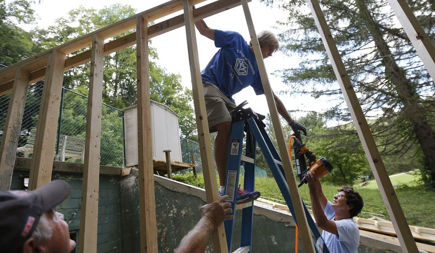 Sandy Clapp reaches down to get the nail gun from Terry Smith while Sandy's brother Bruce Clapp holds up the framing to a new storage shed at Camp Wyandot in Rockbridge, Ohio on Aug. 4, 2016. For the past three summers, a small group of Camp Wyandot alumni and their family and friends have returned to the residential camp in the Hocking Hills to complete construction projects as volunteers. (Columbus Dispatch photo by Jonathan Quilter)