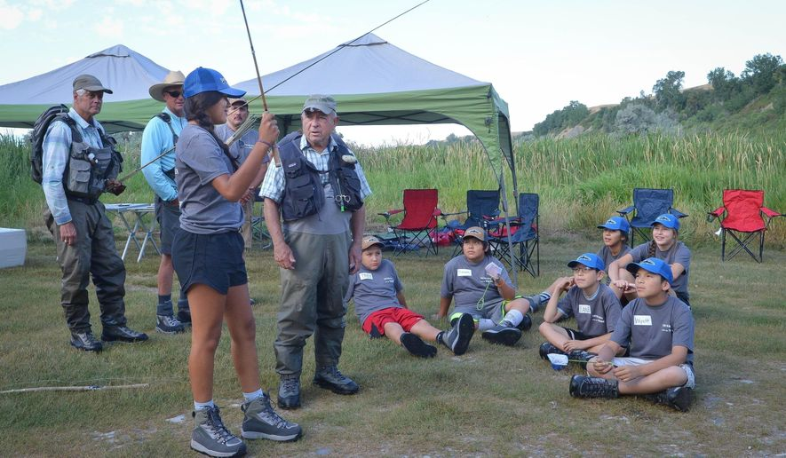 CORRECTS BYLINE TO CHRIS JORGENSEN NOT PETER HERZOG - ADVANCE FOR THE WEEKEND OF AUG. 13-14 AND THEREAFTER - In a July 30, 2016 photo, Yvon Chouinard instructs students on the use of a Tenkara rod, an ancient method of fishing that doesn't require a reel. Ann Marie Emery organized a day of fly fishing on the Bighorn for a group of seven Crow Indian students on a stretch of the river about 10 miles south of St. Xavier. (Chris Jorgensen/Billings Gazette via AP)