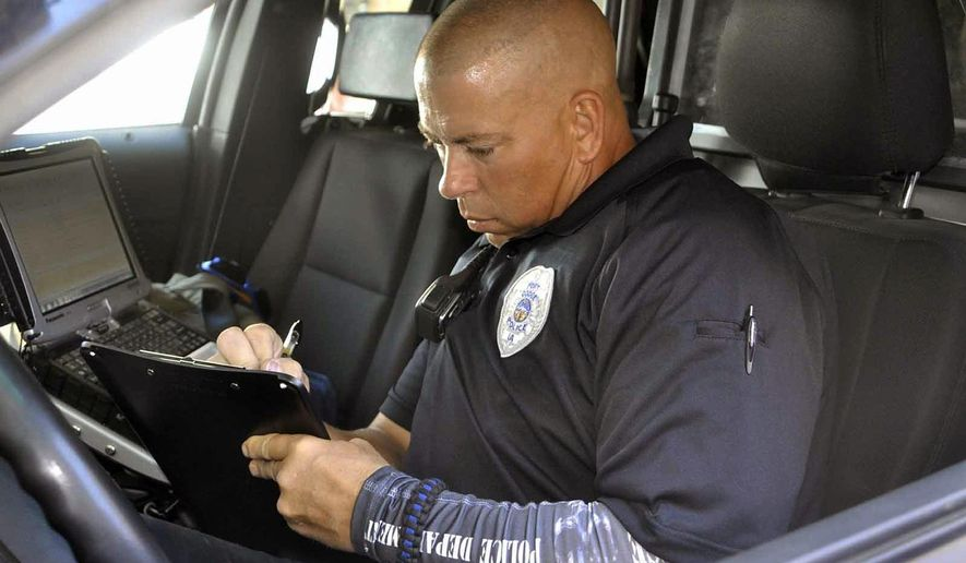 ADVANCE FOR WEEKEND EDITIONS AUG. 13-14 - In this Aug. 5, 2016 photo, Fort Dodge Police Officer Paul Samuelson fills out a report in his patrol car in Fort Dodge, Iowa. During the day, Fort Dodge Police Officer Paul Samuelson patrols the streets of Fort Dodge helping to keep the citizens of the community safe. But at night, Samuelson works at his other job as a police dog trainer. (Peter Kaspari/The Messenger via AP) MANDATORY CREDIT