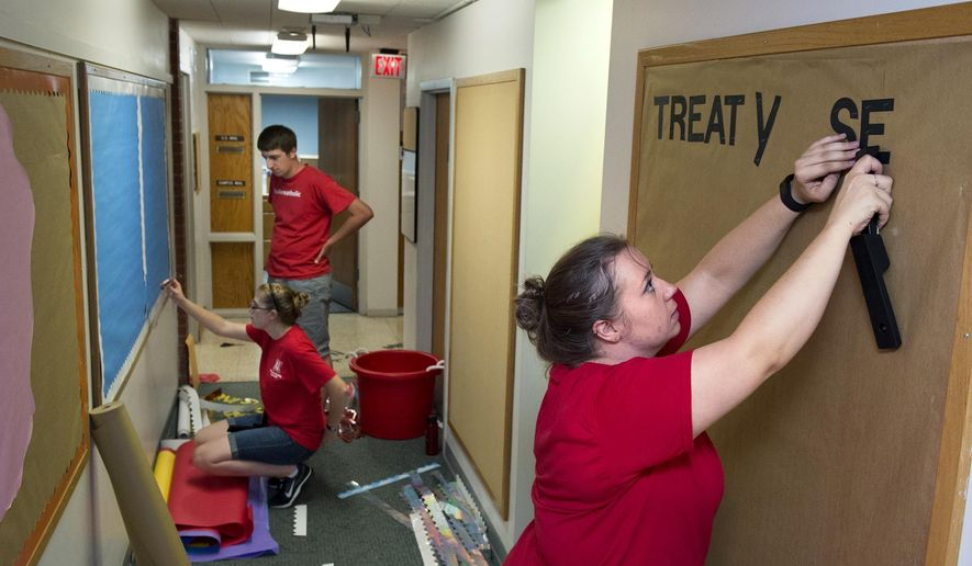 ADVANCE FOR WEEKEND EDITIONS AUG. 13-14 - In this Aug. 10, 2016 photo, University of Nebraska grad student Nicole Swanson, right, works with fellow front desk assistants Brigitte Rathey and Nick Volesky to assemble information boards for Burr Hall residents ahead of move-in in Lincoln, Neb. (Gwyneth Roberts/The Journal-Star via AP)