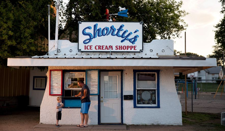 This photo taken July 21, 2016, shows Matt Pelster and his son Liam ordering ice cream from Shorty's in Albion, Neb. Shorty's serves up guilty pleasure. But this tiny snack shack in a town two hours northwest of Omaha also is offering something else: the past. (Ryan Soderlin/The World-Herald via AP)