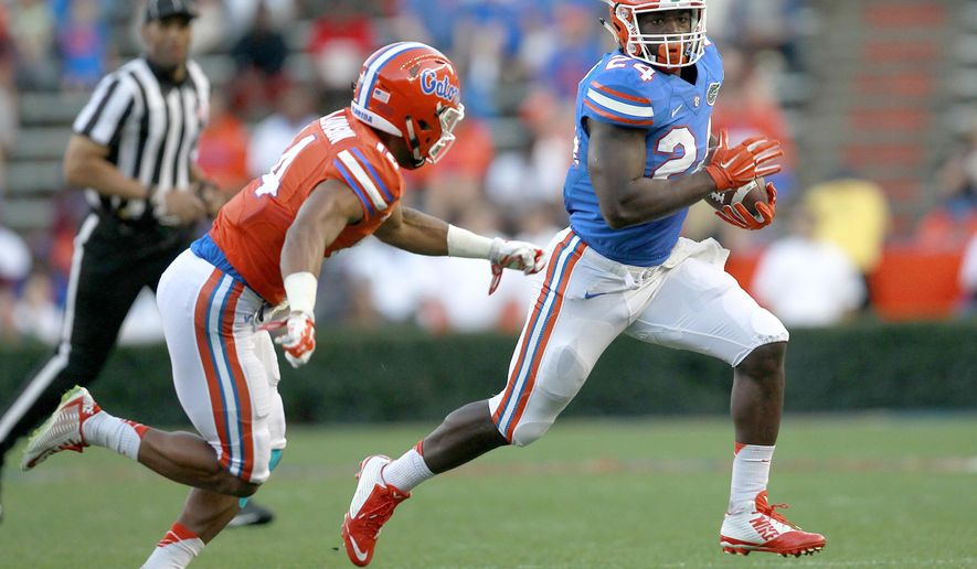 FILE - In this April 8, 2016, file photo, Florida running back Mark Thompson runs upfield past defensive back Chris Williamson during a spring NCAA college football game in Gainesville, Fla. The junior college transfer wants to have 1,000 yards rushing through seven games. That's fairly high-reaching, especially for someone who isn't the starter, has never played a down in the Southeastern Conference and has plenty of competition for carries. (Matt Stamey,/The Gainesville Sun via AP, File)