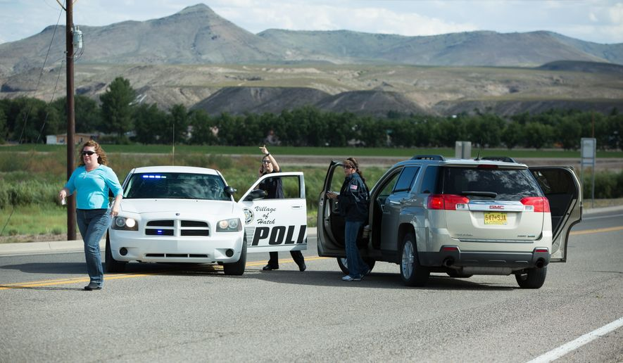 Police officers and state employees prevent drivers from entering Hatch, N.M., after a shooting on Friday, Aug. 12, 2016.   Dona Ana County authorities say a Hatch police officer has died after being shot during a traffic stop on Friday.    (Anayssa Vasquez/The Las Cruces Sun-News via AP) MANDATORY CREDIT