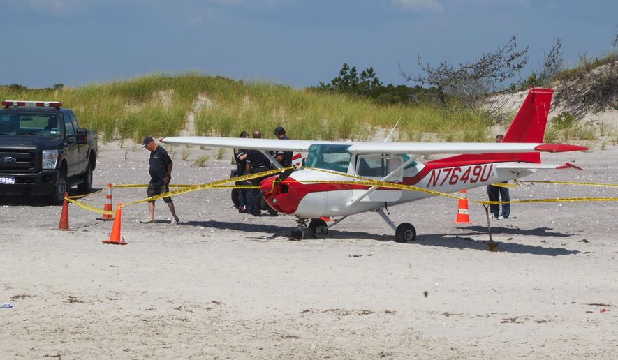 Authorities gather near a light airplane that made an emergency landing on the beach at Smith Point County Park in Shirley, N.Y., Saturday, Aug. 13, 2016. There are no immediate reports of any injuries. (Ed Betz/Newsday via AP)