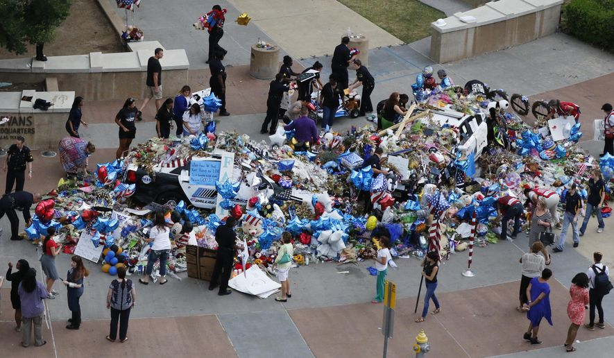 FILE - In this July 15, 2016 file photo, Dallas Police officers and volunteers help pick up notes, flowers, balloons and other items at a memorial at the Dallas police headquarters before a rain storm.   Library archive experts have carefully sorted and saved items left outside the headquarters after last month's fatal shooting of five officers. Many objects will eventually be added to the Dallas History and Archive Collection.  (David Woo/The Dallas Morning News via AP)