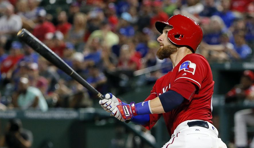 Texas Rangers' Jonathan Lucroy watches the flight of his two-run home run off Detroit Tigers' Anibal Sanchez during the third inning of a baseball game, Friday, Aug. 12, 2016, in Arlington, Texas. (AP Photo/Tony Gutierrez)
