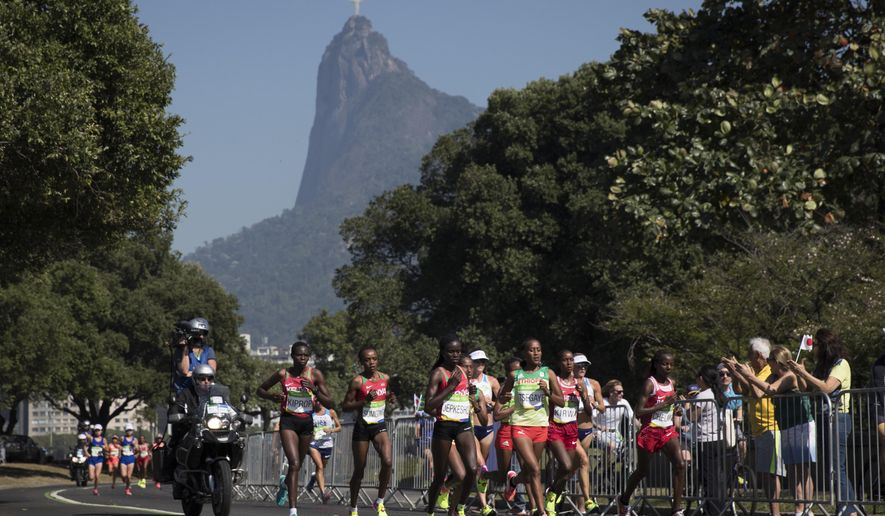 Athletes compete backgrounded by the Christ the Redeemer statue and Corcovado mountain in the women's marathon at the 2016 Summer Olympics in Rio de Janeiro, Brazil, Sunday, Aug. 14, 2016. (AP Photo/Felipe Dana)