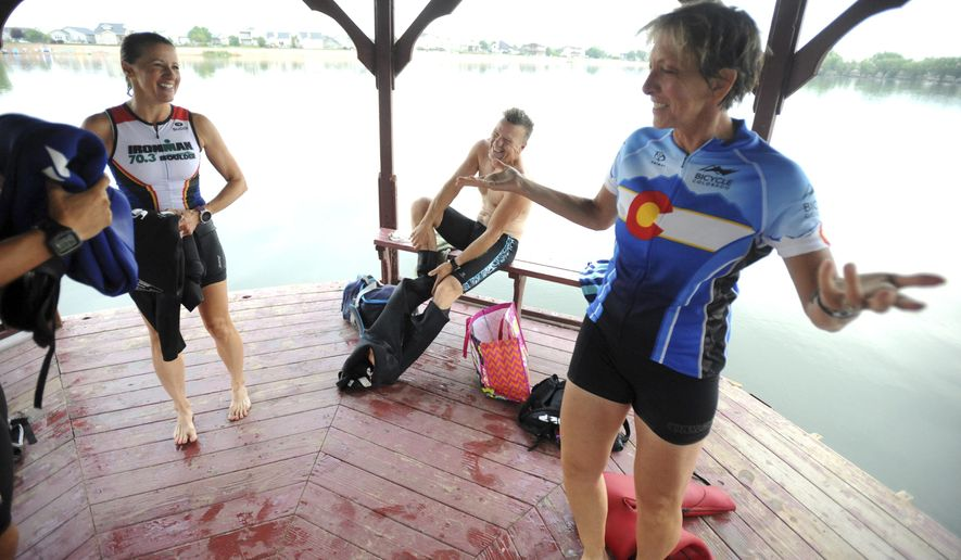 ADVANCE FOR WEEKEND EDITIONS AUG. 13-14 - In this Aug. 5, 2016 photo, Cindy Dallow laughs after her training group finishes swimming a lap around Pelican Lake in Windsor, Colo. There's a surprising amount of traffic on Highway 257 at 5:45 a.m., but just off the road, down at Pelican Lakes, it seems the only thing awake besides the carp jumping out of the water is the Greeley Triathlon Club. (Joshua Polson/The Greeley Tribune via AP)