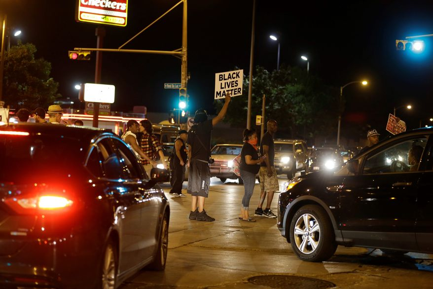 Protesters block traffic at a busy intersection Sunday in Milwaukee. (Associated Press)