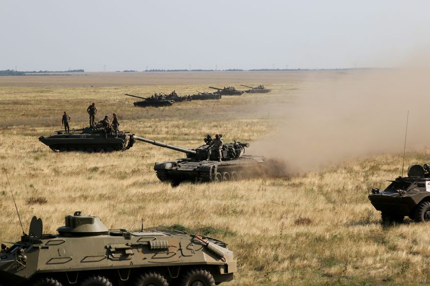 Ukraine put its troops on combat alert Thursday along the country's de-facto borders with Crimea and separatist rebels in the east amid an escalating war of words with Russia. (Associated Press)
