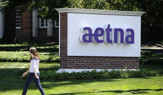 A woman walks past a sign for health insurer Aetna Inc., at the company headquarters in Hartford, Conn. (Associated Press)