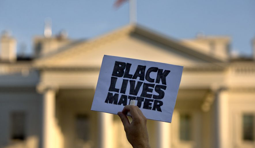 """In this July 8, 2016, file photo, a man holds up a sign saying """"Black Lives Matter"""" during a protest of shootings by police, at the White House in Washington. (AP Photo/Jacquelyn Martin) ** FILE **"""
