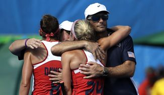 United States coach Craig Parnham, right, hugs his team player Kathleen Sharkey, as he comforts his team after they lost 2-1 against Germany, during a women's field hockey quarterfinal match at 2016 Summer Olympics in Rio de Janeiro, Brazil, Monday, Aug. 15, 2016. (AP Photo/Hussein Malla)
