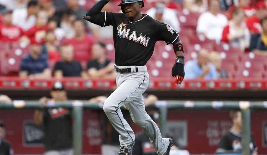 Miami Marlins' Dee Gordon holds his helmet as he scores on on a Martin Prado single against the Cincinnati Reds during the first inning of a baseball game, Monday, Aug. 15, 2016, in Cincinnati. (AP Photo/Gary Landers)