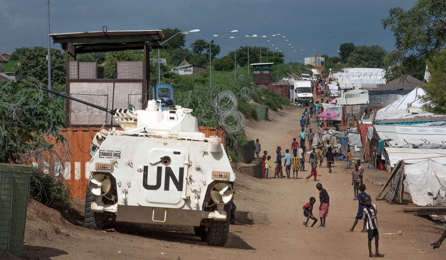 In this Monday, July 25, 2016, file photo, some of the more than 30,000 civilians, sheltering in a United Nations base in South Sudan's capital Juba for fear of targeted killings by government forces, walk by an armored vehicle and a watchtower manned by Chinese U.N. peacekeepers. (AP Photo/Jason Patinkin, File) **FILE**