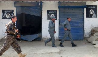 Afghan police walk past Islamic State militant flags after an operation in the Kot district of Jalalabad province in Afghanistan on Aug. 1. (Associated Press)