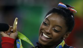 United States' Simone Biles displays her gold medal for floor during the artistic gymnastics women's apparatus final at the 2016 Summer Olympics in Rio de Janeiro, Brazil, Tuesday, Aug. 16, 2016. The World Anti-Doping Agency (WADA) on Sept. 13 said a Russian espionage group was behind a cybersecurity breach that resulted in the private health records of U.S. Olympic athletes being leaked online, including that of Ms. Biles. (AP Photo/Rebecca Blackwell)