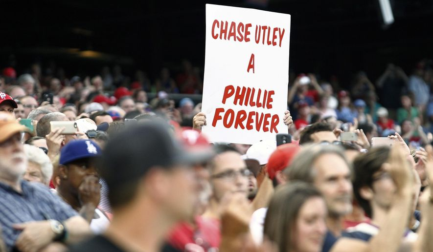 A fan holds up a sign for Los Angeles Dodgers' Chase Utley as he comes to bat during the first inning of a baseball game against the Philadelphia Phillies, Tuesday, Aug. 16, 2016, in Philadelphia. Utley was a member of the Philles' championship team in 2008 and a favorite of the fans for the years he played on the team.. (AP Photo/Tom Mihalek)