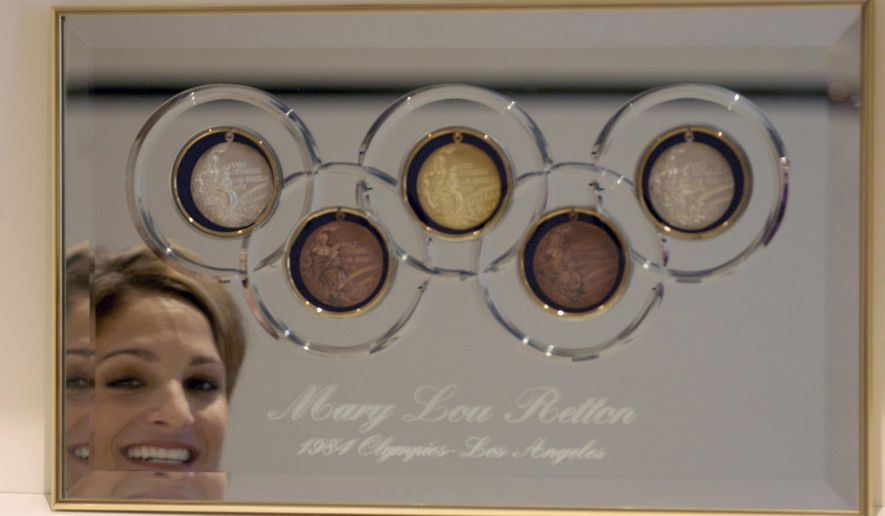 "This photo taken Aug. 11, 2004, shows May Lou Retton reflected in her five Olympic medals that are on display in her home. Simone Biles has won more world championships, Nastia Liukin has as many Olympic medals and Shannon Miller has more world and Olympic medals combined. And yet, more than 30 years later, the Sports Illustrated headline of Aug. 13, 1984, rings true: ""Only You, Mary Lou.""  (E. Joe Deering/Houston Chronicle via AP)"